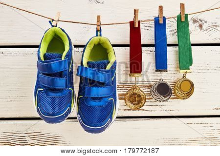 Sneakers and medals on clothesline. My sport achievements.
