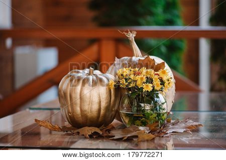 Golden decorated pumpkin with the yellow flowers in the vase
