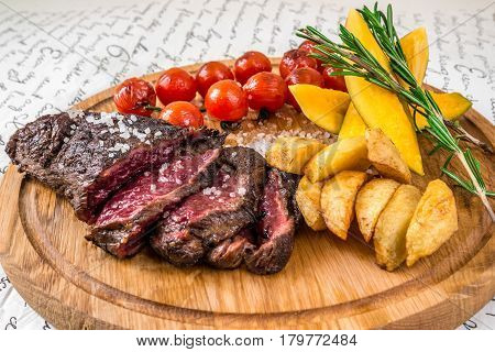 Mixed grilled meat potatoes tomatoes with herbs on a wooden board