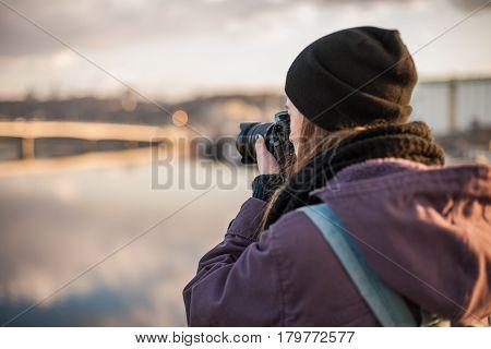 Female traveler photographer taking photos of cityscape