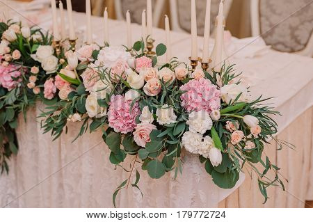 Wedding table decoration with roses, carnations and candles for the fiance and fiancee in the tenderly light pink style