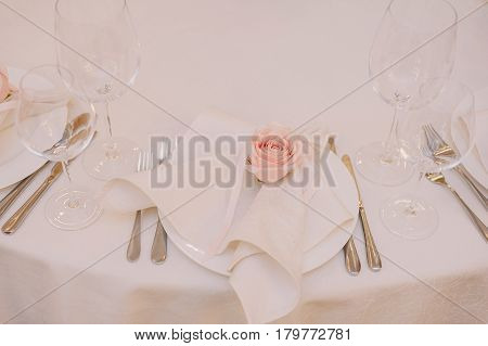 Wedding table decoration of the napkin with the light pink rose on the plate for the guests