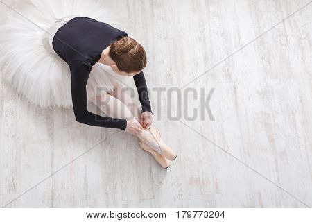 Graceful young ballerina in pointe shoes at white wooden floor background, top view from above with copy space. Ballet practice and stretching. Back of ballet dancer.