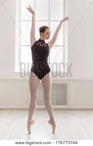 Classical Ballet dancer training. Beautiful graceful ballerina in black on pointe near large window in light hall. Ballet class, high-key soft toning. Vertical image