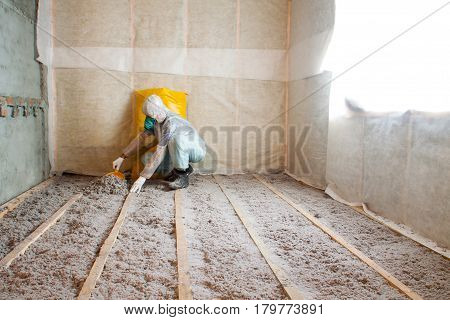 Work composed of cellulose insulation in the floor, floor heating insulation , warm house, eco-friendly insulation, insulation paper, a builder at work