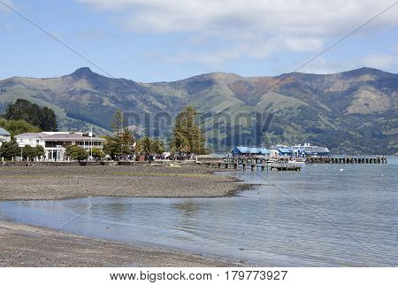 The view of Akaroa resort town beach by French Bay (New Zealand).