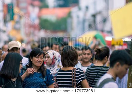 Blurred Image Of A Crowd Of People At A Street Market. Malacca, Malaysia, 07/10/2016