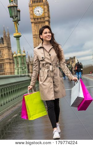 Happy girl or young woman walking with shopping bags on Westminster Bridge with Big Ben in the background, London, England, Great Britain