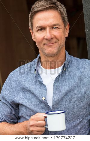 Portrait shot of an attractive, successful and happy middle aged man male wearing a blue shirt drinking tea or coffee from a tin cup