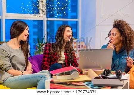 Giggly friends speaking with each other while sitting in apartment. They are in good mood. Fine concept