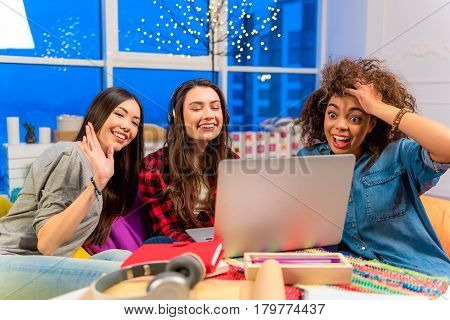 Astonishing african female watching at screen. She sitting near friends. Girls speaking with person from computer. Astonishment concept