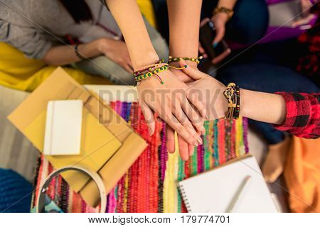 Friends forever. Close up top view of three girls putting arms together. Women showing team spirit. Friendship concept