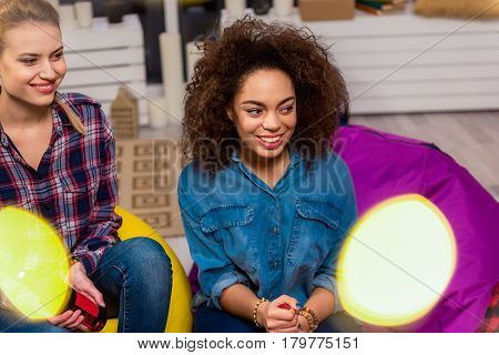 African and caucasian women expressing gladness while sitting in apartment. They looking away