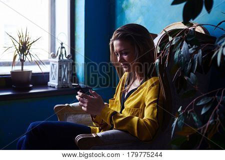 Side view shot of a carefree positive brunette sitting in an armchair with a smartphone. Obscure atmosphere. Window next to the armchair. Home interior