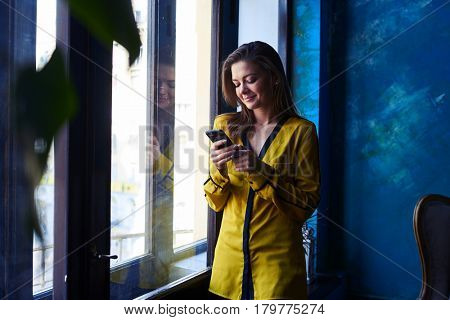Close-up shot of a stylish modern woman standing with mobile telephone near the window. Smiling while chatting with someone. Using telephone