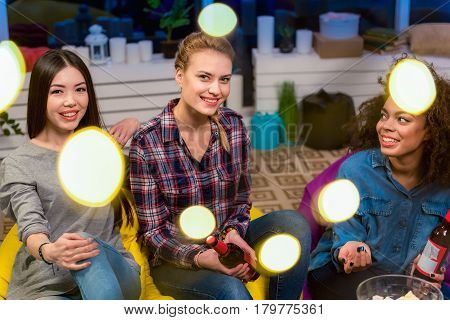 Party for girls only. portrait of smiling friends tasting beer while leaning on chair
