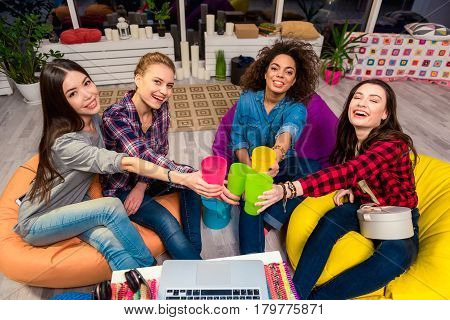 Top view of cheerful asian, african and caucasian women tasting soft drink in apartment