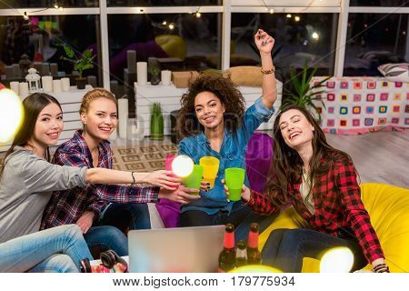 outgoing female friends clanging glasses together during party indoor. They looking at camera