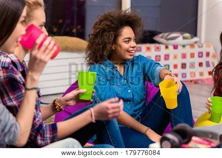 Focus on side view portrait of outgoing african girl telling with friend. She looking at her while drinking beverage