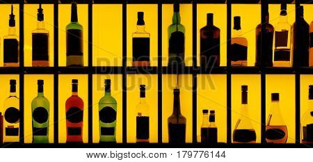Various hard alcohol bottles in a bar, yellow back lighting