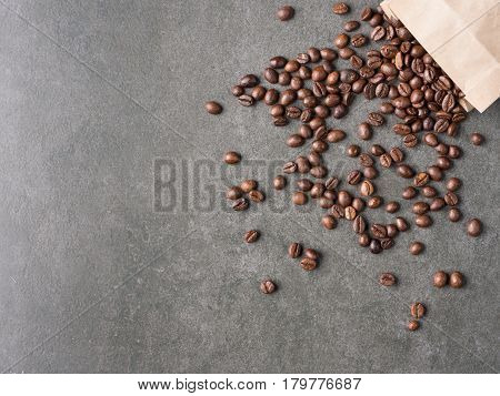 Roasted coffee beans scattered from paper bag over dark gray granite plate captured from top view with sharp focus