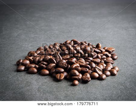 Roasted coffee beans over dark gray granite plate captured from top view with sharp focus