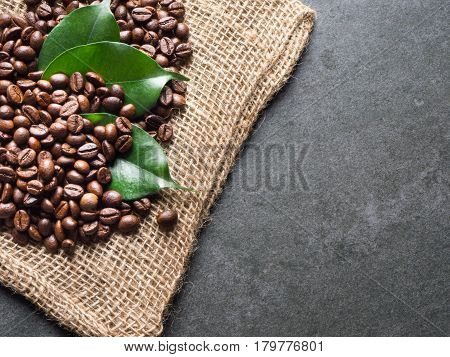 Coffee beans with green leaves on sack and dark gray granite plate captured from top view