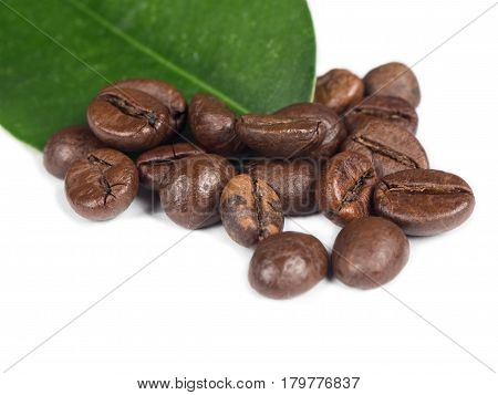 Pile of coffee grains with green leaf over white isolated background.