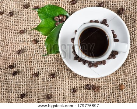 White cup filled with hot coffee roasted beans and green leaves scattered around the cup and sack for background captured from top view with sharp focus