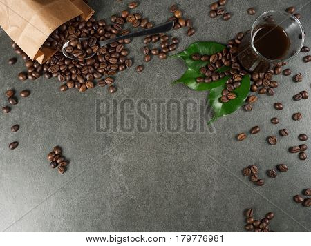 Glass filled with hot coffee roasted beans little spoon and green leaves scattered from paper bag. Dark gray granite for background captured from top view with sharp focus