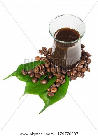 Glass filled with hot coffee roasted beans and green leaves scattered around. White isolated background captured from top view with sharp focus