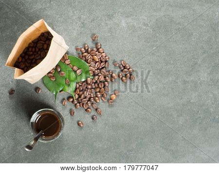 Glass filled with hot coffee roasted beans and green leaves scattered from paper bag. Dark gray granite for background captured from top view with sharp focus