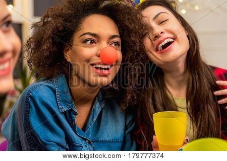 Attractive happy woman looking away while sitting near comrades. She wearing clownish nose while having fun. Joke concept