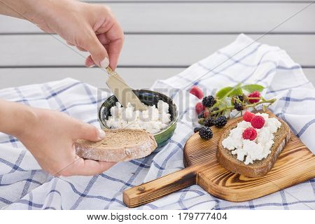 Woman taking organic farming cottage cheese from green bowl. Breakfast: slice of whole wheat bread with Homemade Ricotta cheese served with raspberries and blackberries on wooden board on linen fabric