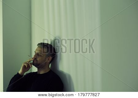 Depressed thoughtful man holding a cigarette in dark room