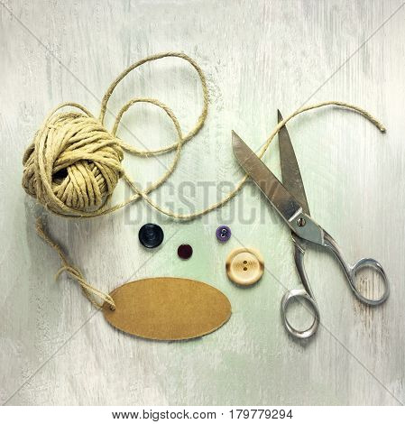 A square photo of vintage scissors with a roll of twine, a tag with copy space, and buttons, shot from above on light wooden boards background texture