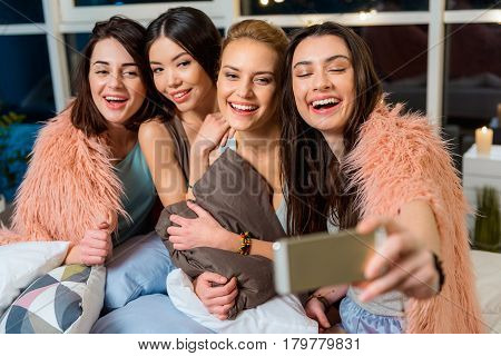 Cheerful female friends doing photographs at mobile. They spending good time at pajama party