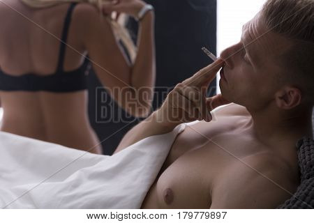 Young Man Smoking Cigarette After Sex