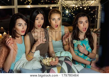 It is very interesting moment. Astonishing asian and caucasian girls watching movie with big excitement at home