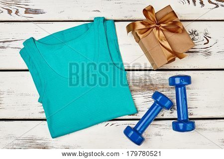 Tank top and dumbbells. Present for active girl.