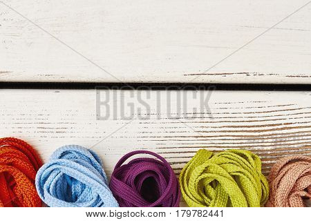 Multicolored shoelaces on wooden background. Stylish footwear accessories.