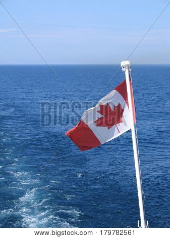 A wake of water trails a sunlit Canadian flag flying from the stern of a boat in Georgian Bay, Ontario, Canada.