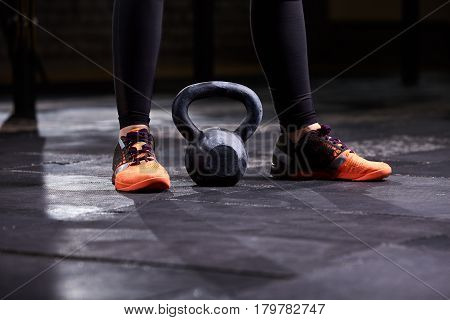 Cropped image of young woman, legs in the black leggings, orange sneakers and kettlebell. Crossfit workout. Closeup. Detail. Sneakers. Healthy lifestyle.