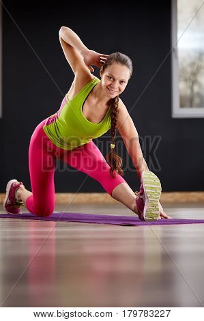 Slim athletic woman working out in gym doing knee-bounce exercise or lunges. Yoga woman in the sporty clothes, pink leggings and green t-shirt. On the violet yoga mat.