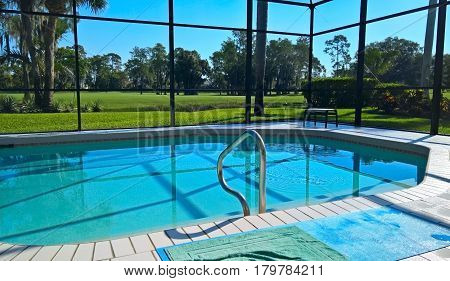 A view of the swimming pool in a house in Florida in the middle of Naples golf course with grass and palm trees under a blue sky on a sunny day