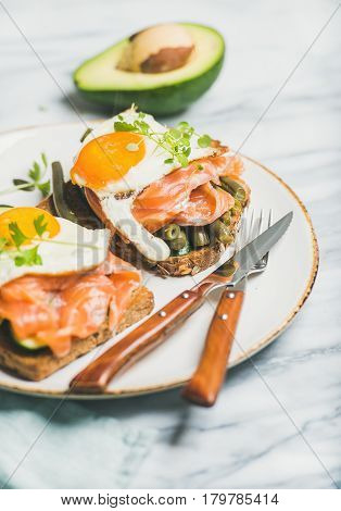 Healthy breakfast sandwiches. Salmon, avocado, fried egg, sauted green beans and fresh sprouts sandwiches in white plate over marble background, selective focus. Clean eating, dieting food concept