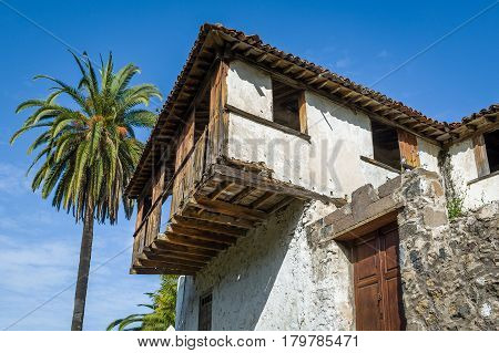 Old house at Icod de los Vinos and palm tree. Tenerife island, Spain.