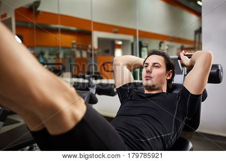 Athletic man in the black sportwear doing exercises on legs in gym. Fitness and Sport. Sportsman in the t-shirt and shorts. Power and energy. Interior of gym with mirrors. Healthy lifestyle.