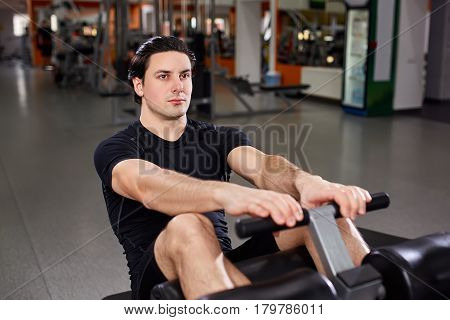 Fitness athlete doing exercises on vertical bench press machine with hands and legs. Man exercising at gym. Sportsman in the black sportwear, t-shirt and shorts. Healthy lifestyle. Interior of gym.