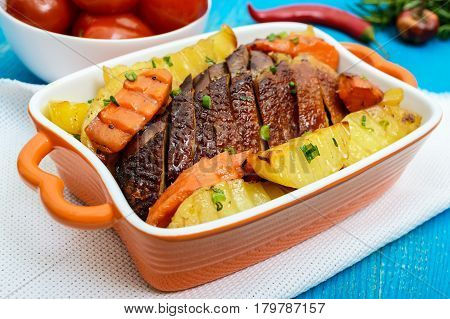 Roasted fillet of brisket goose sliced potatoes rustic in a ceramic bowl with marinated tomatoes on a blue wooden background.